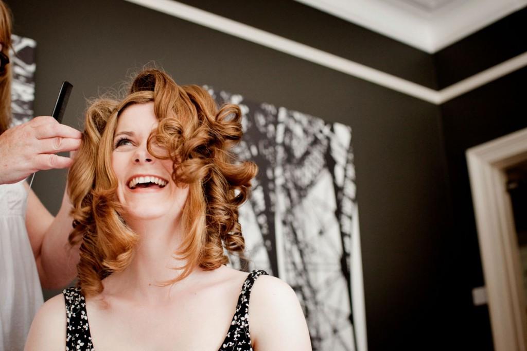 Bridebook.co.uk- bride laughing while having her hair done