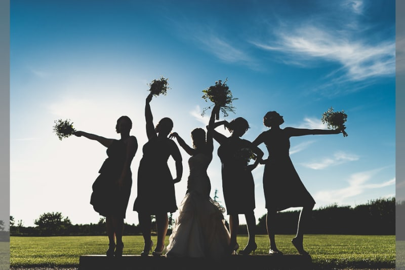 Bridebook.co.uk- bride and bridesmaids silhouetted against the sun holding up their bouquets
