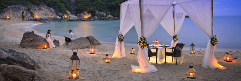 Bridebook.co.uk- bride and groom having romantic dinner on beach