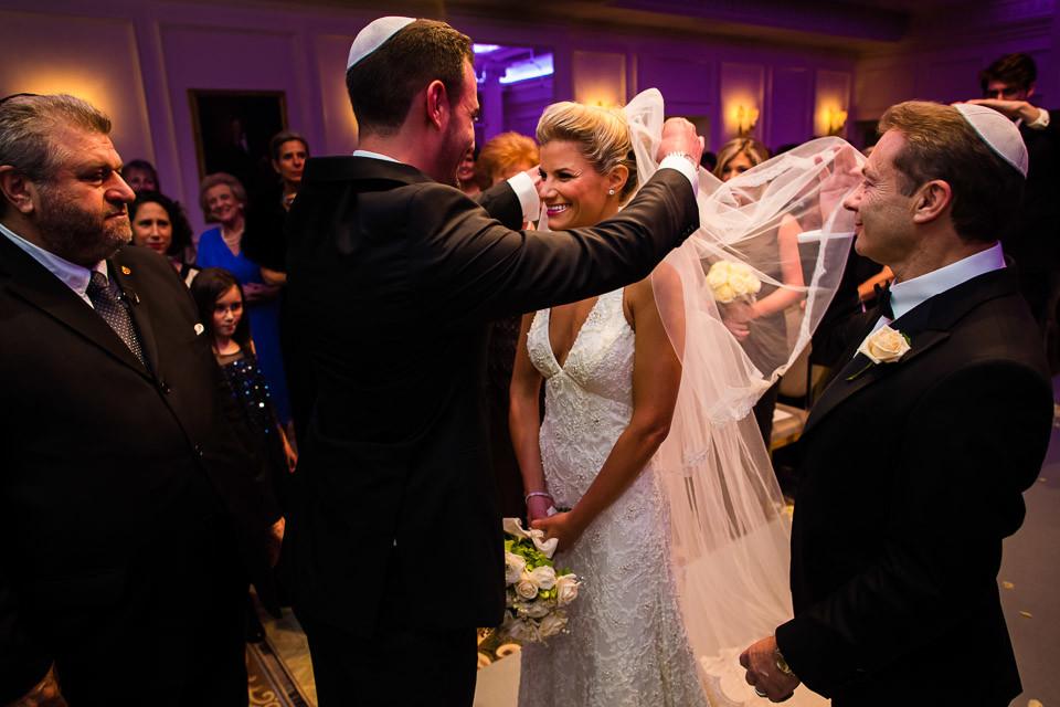 Bridebook.co.uk- Groom lifting bridal veil at Jewish wedding ceremony