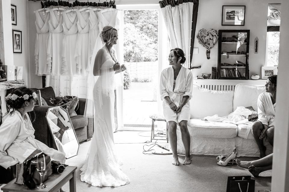 www.bridebook.co.uk bride in her dress as bridesmaid looks on smiling