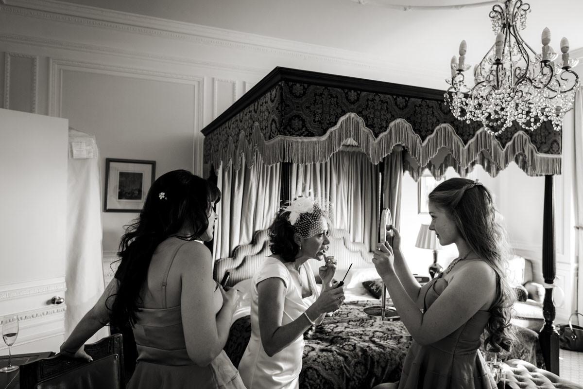 www.bridebook.co.uk bride applying lipstick as bridesmaids hold up a mirror