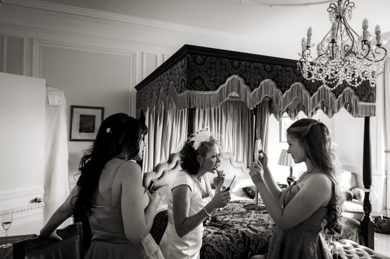 www.bridebook.co.uk bride applying lipstick as bridesmaids hold up a mirror