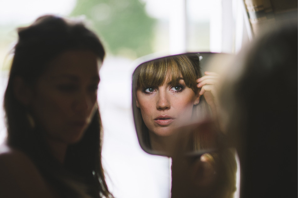 www.bridebook.co.uk bride checking her make up in the mirror