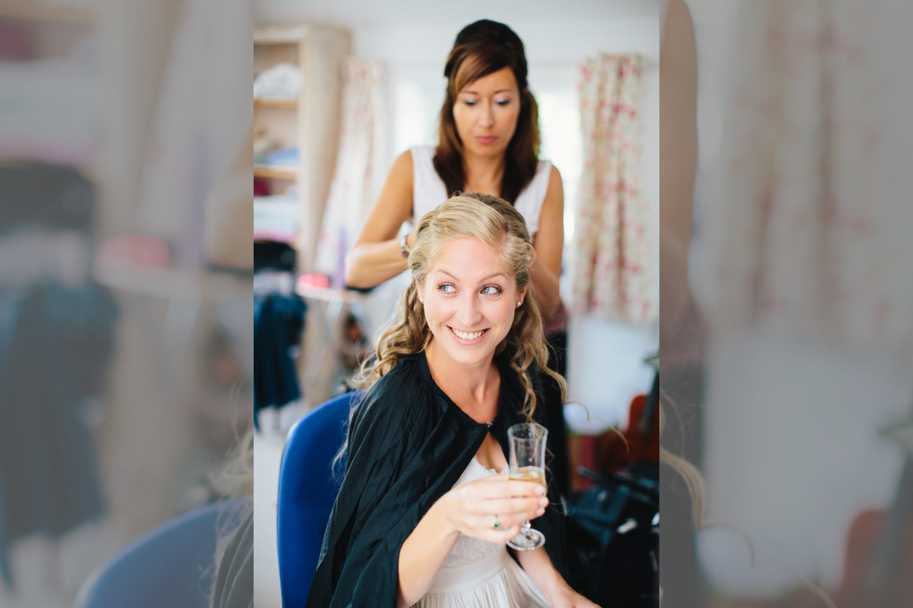 www.bridebook.co.uk bride having her hair done and drinking champagne