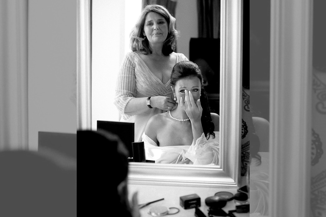 Bridebook.co.uk- mother and bride tearing up reflection in the mirror