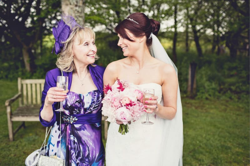 Bridebook.co.uk- mother and bride smiling at each other holding glasses of champagne
