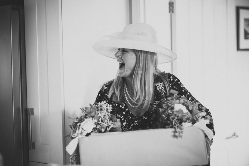 Bridebook.co.uk- mother of the bride laughing and carrying a box of flowers