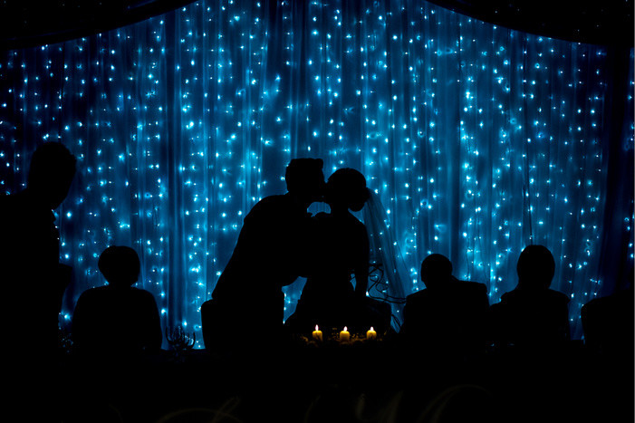 Bridebook.co.uk- bride and groom kiss against a lit up abckground