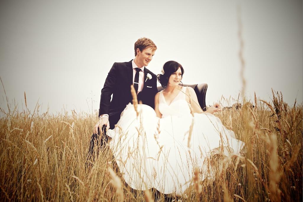 Bridebook.co.uk- bride and groom in an armchair in a field