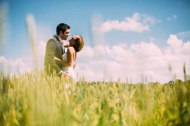 Bridebook.co.uk- bride and groom hugging and laughing in a field