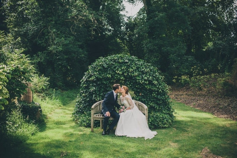 Bridebook.co.uk- bride and groom kissing under green arch