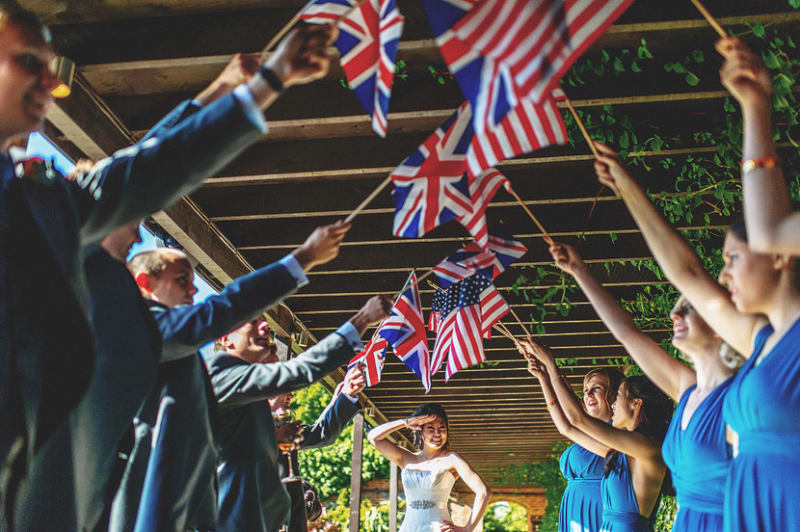 Bridebook.co.uk- bride standing under american and british flags held by wedding team