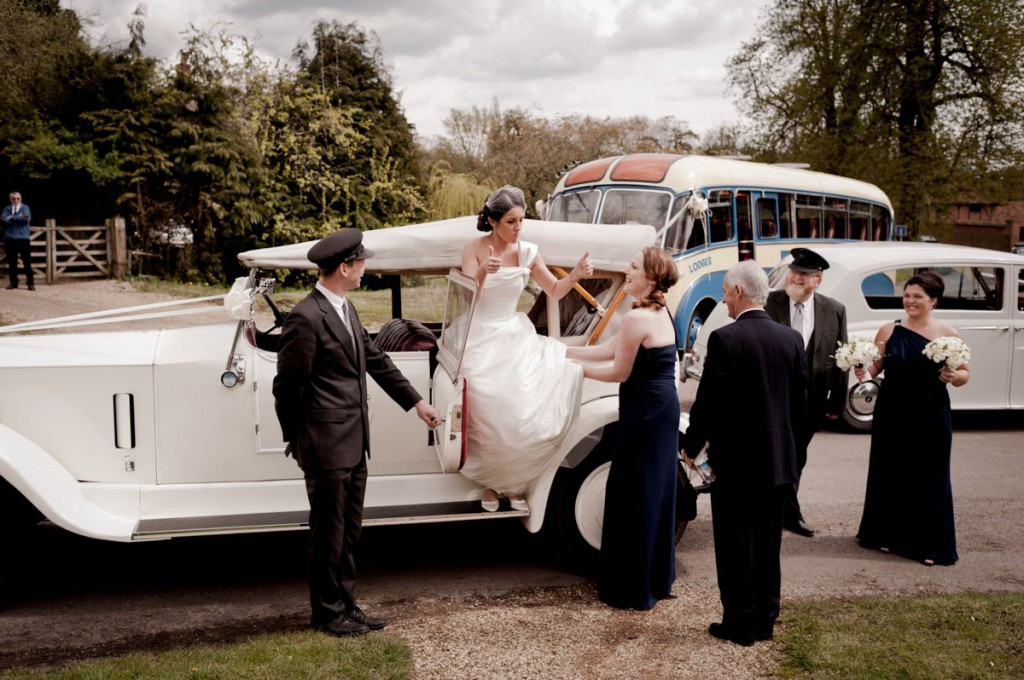 Bridebook.co.uk- bride giving thumbs up to bridal party as she gets out of wedding car