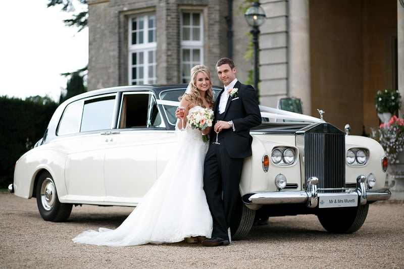 Bridebook.co.uk- couple posing for a photo in front of white wedding car