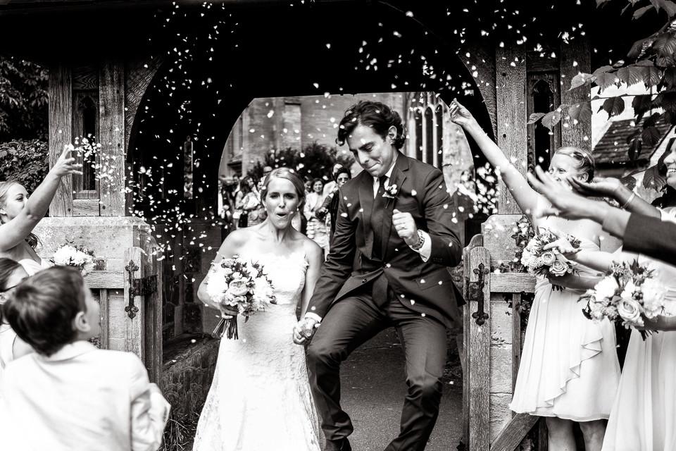 Bridebook.co.uk- groom jumping in the air as bride and groom leave ceremony