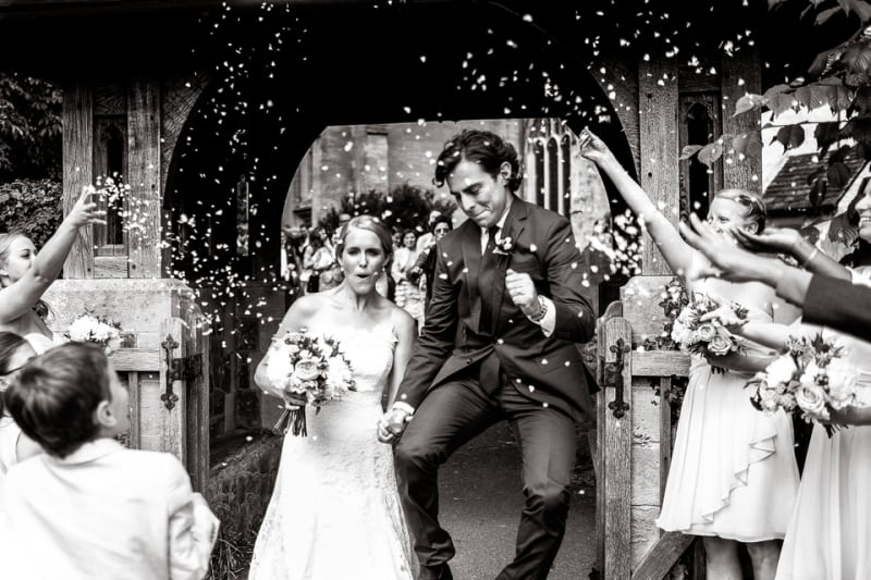 Bridebook.co.uk- groom jumping in the air as bride and groom leave ceremony