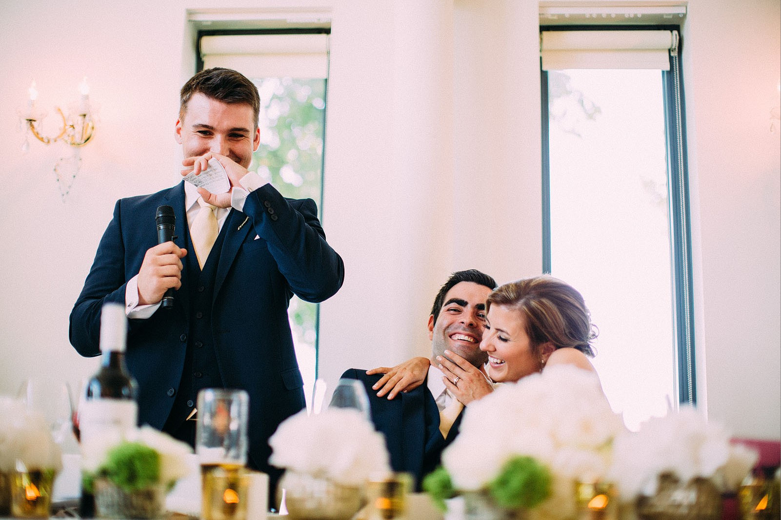 Bridebook.co.uk- best man giving speech as bride and groom hug
