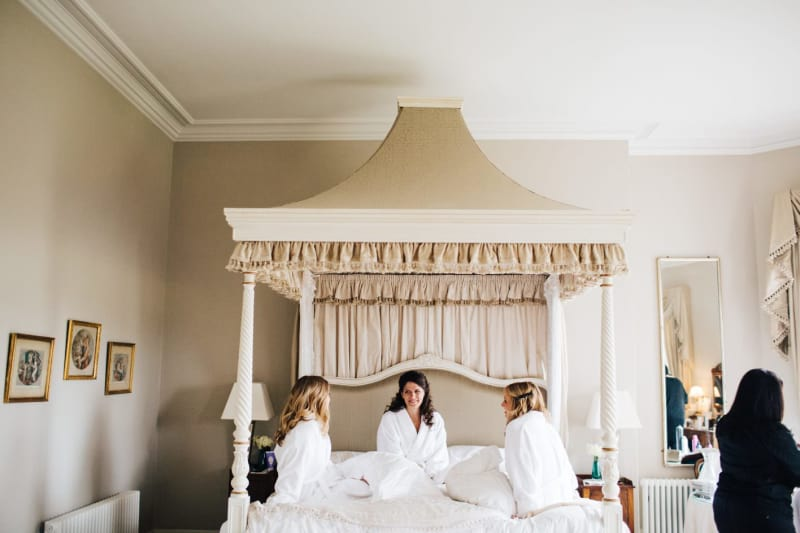 Bridebook.co.uk- bride and bridesmaids chatting in the bridal suite dressed in bathrobes