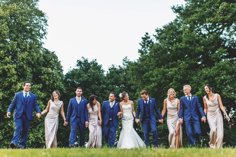 Bridebook.co.uk-  bride groom bridal party and ushers holding hands