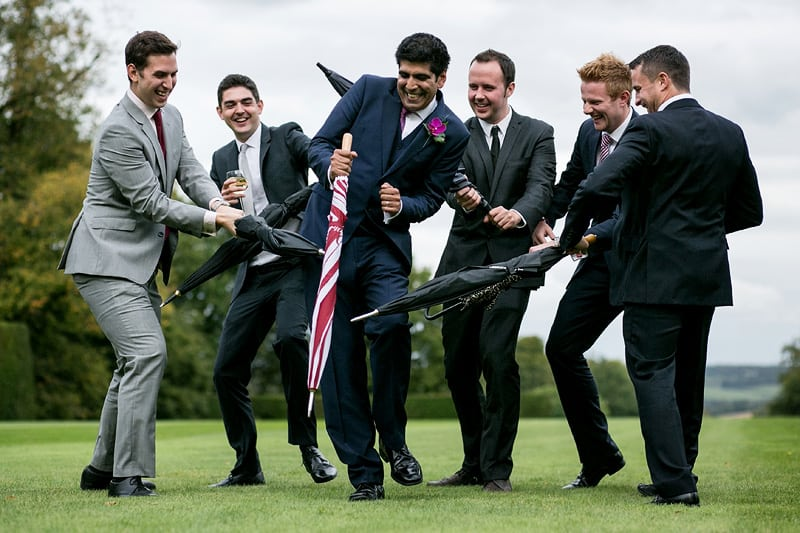 Bridebook.co.uk- groom and ushers play fighting with umbrellas