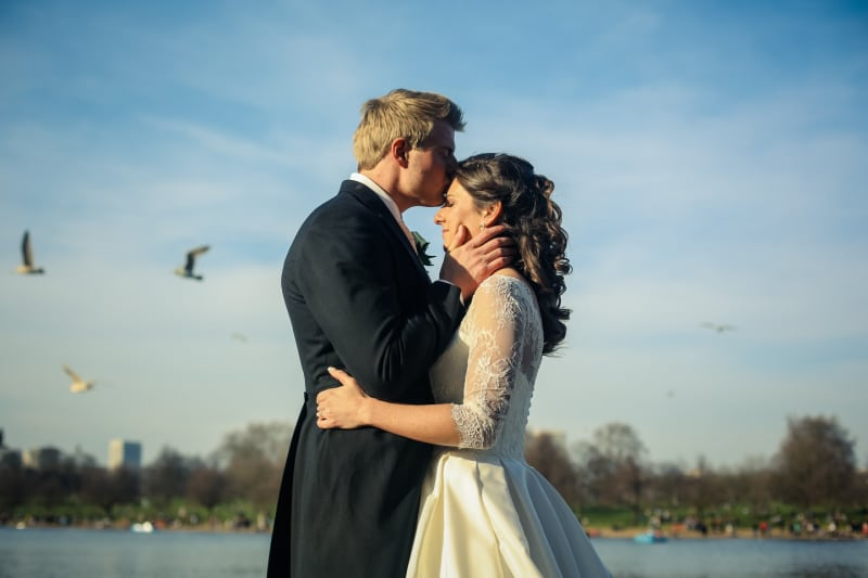 Bridebook.co.uk- groom kissing bride on the forehead by the serpentine lake