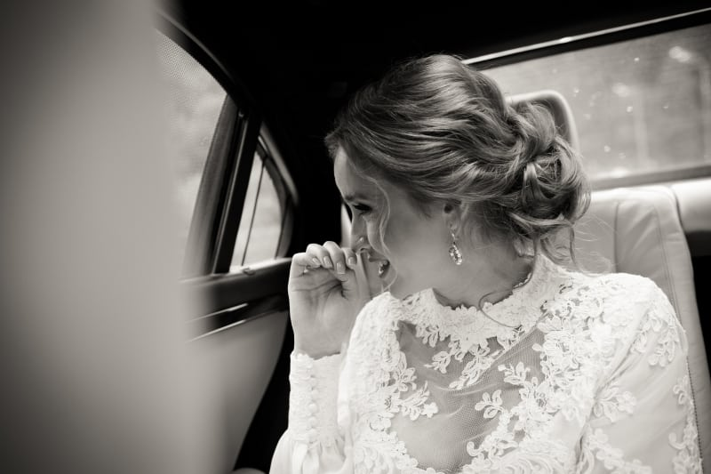 Bridebook.co.uk bride in car in high neck wedding dress and jewellery
