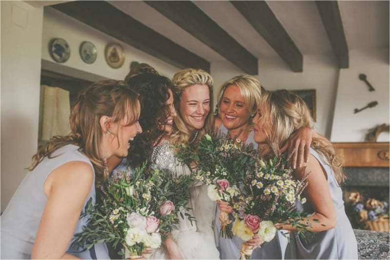 Bridebook.co.uk- bride and bridesmaids hugging and holding bouquets