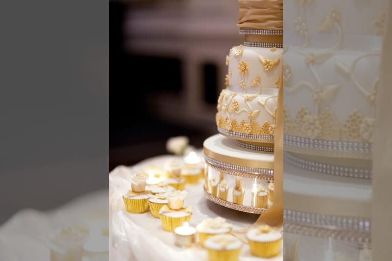 Bridebook.co.uk- gold and white cake with cupcakes