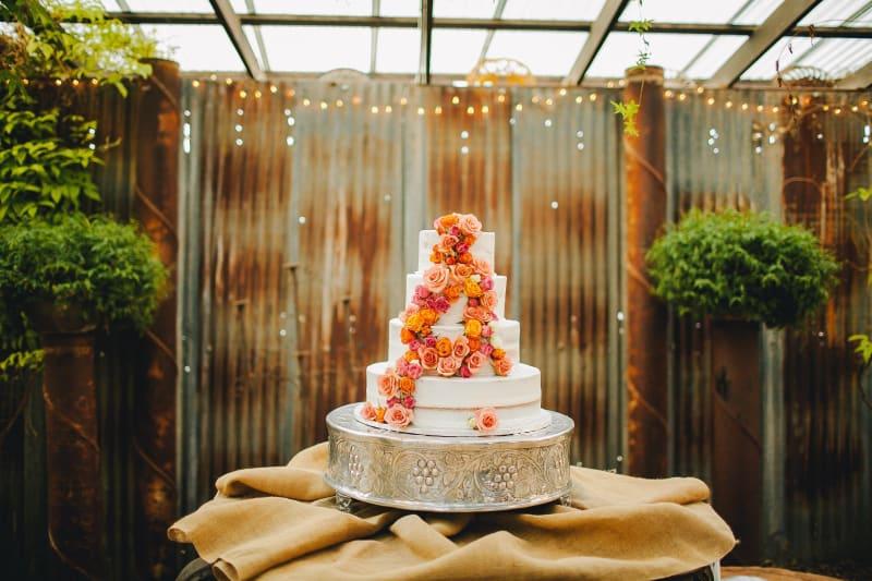 Bridebook.co.uk White Buttercream wedding cake with orange and fuschia flower decoration