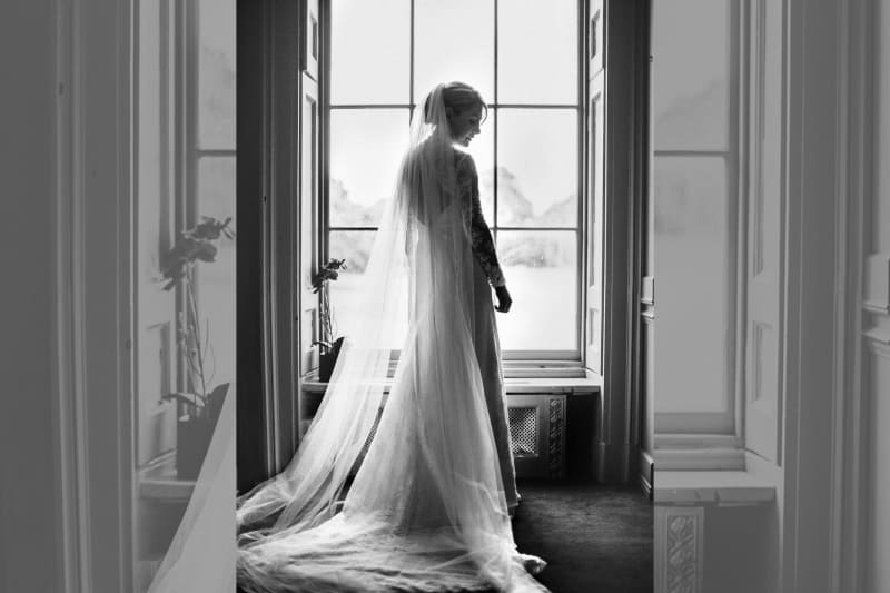Bridebook.co.uk- bride standing next to the window in her dress and cathedral veil