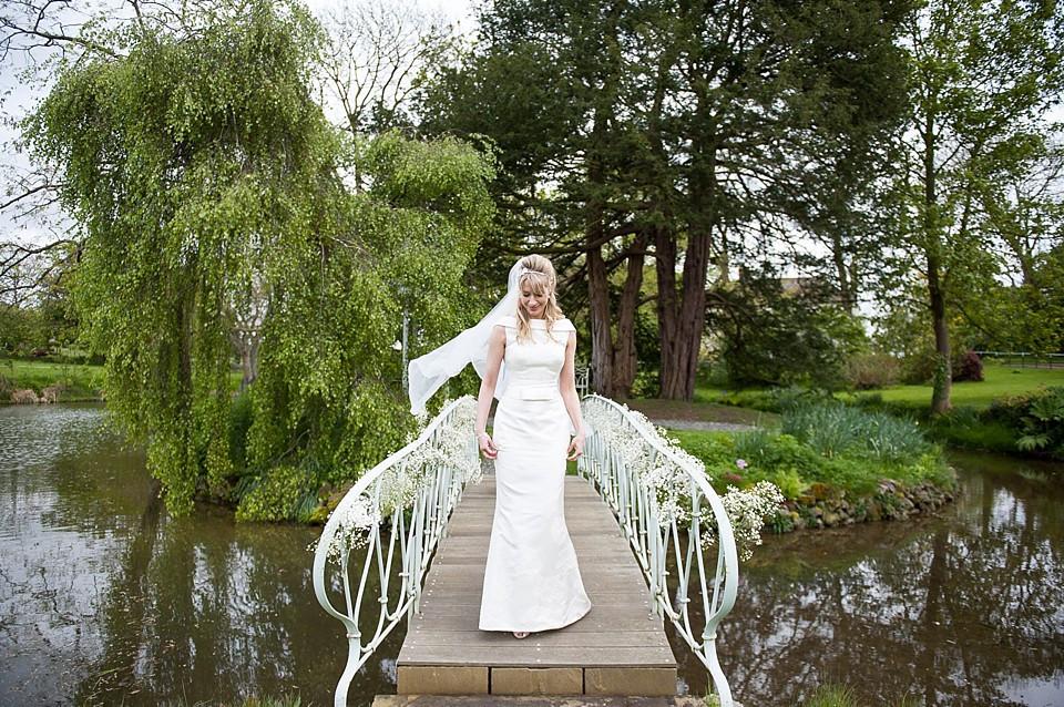 Bridebook.co.uk- bride standing on a bridge running over a lake