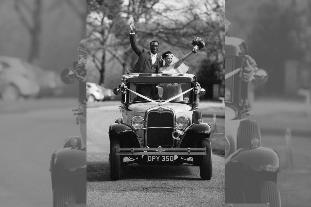 Bridebook.co.uk- bride and groom standing in their wedding car