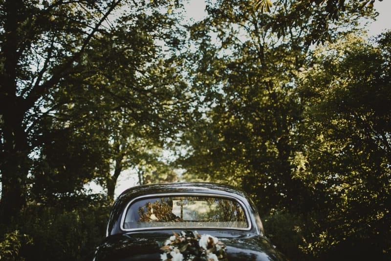 Bridebook.co.uk Vintage car just married under trees