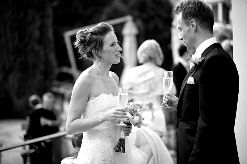 Bridebook.co.uk- bride and groom talking and drinking champagne