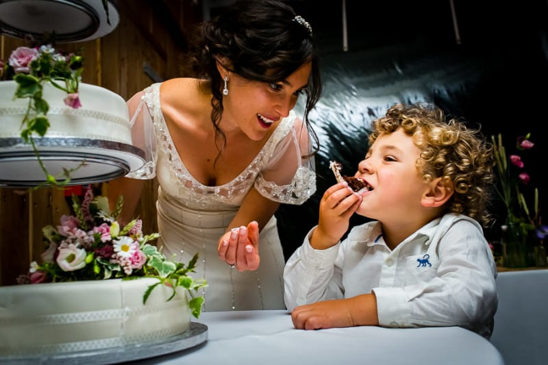 Bridebook.co.uk- bride and little boy chatting next to cake