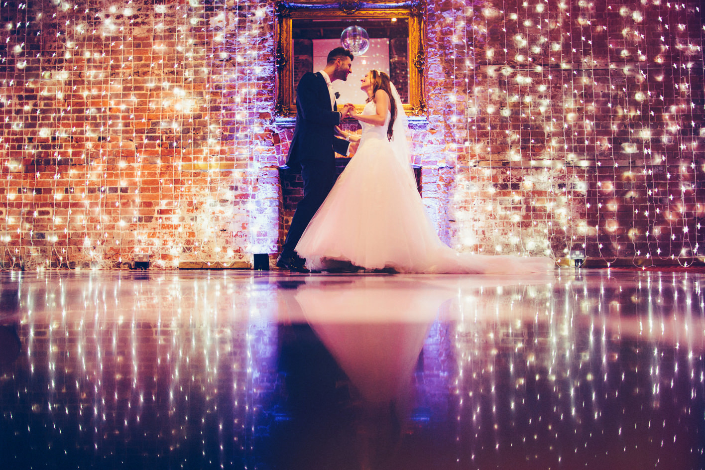 Bridebook.co.uk- bride and groom against fairy lights