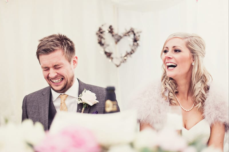Bridebook.co.uk- groom cringing bride laughing during the speeches