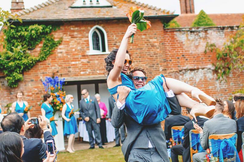 Bridebook.co.uk- usher carrying bridesmaid both wearing sunglasses