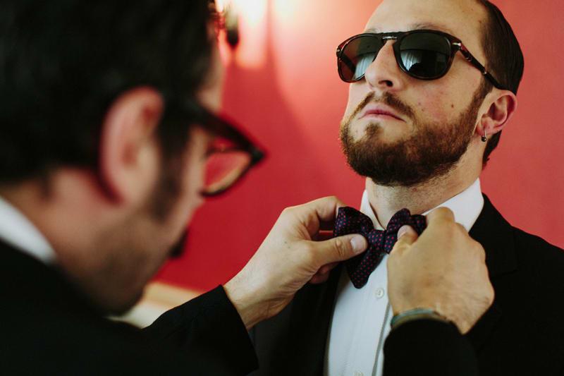 Bridebook.co.uk- usher tying grooms bow tie