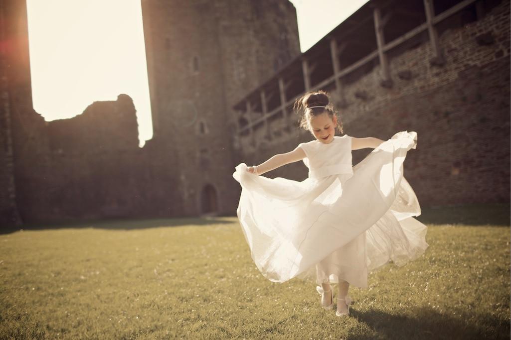 Bridebook.co.uk- flower girl twirling in white dress