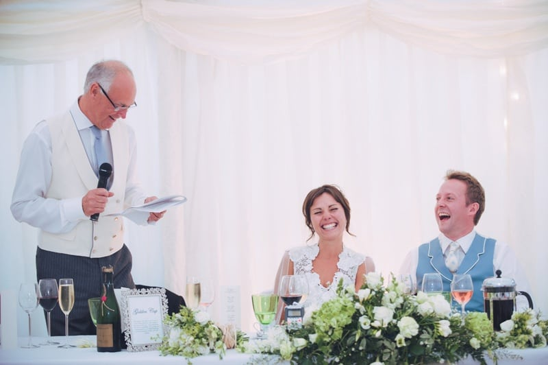 father of the bride reading his speech as bride and groom laugh