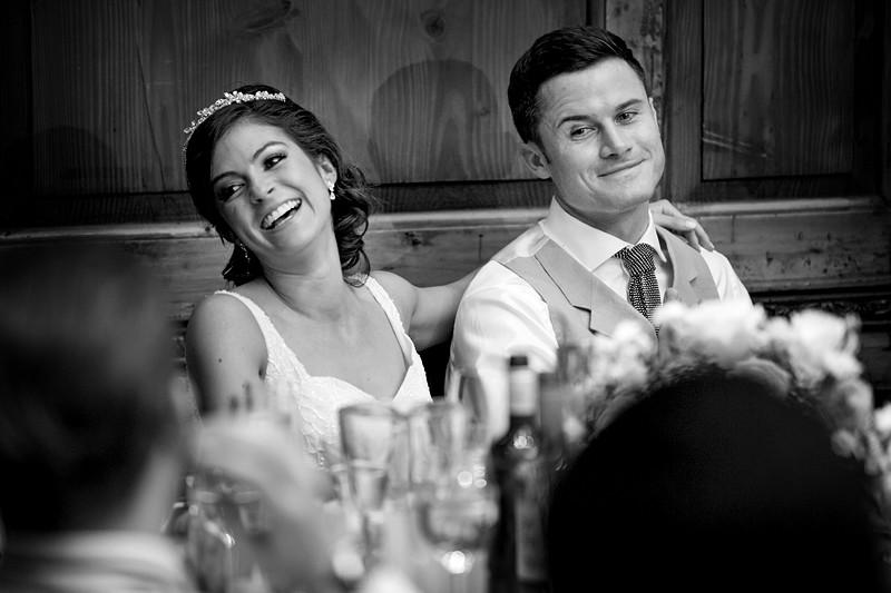 Bridebook.co.uk- bride and groom listening to speeches smiling