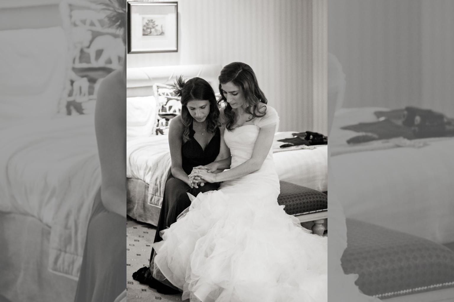Bridebook.co.uk- bride and maid of honour sitting down and holding hands
