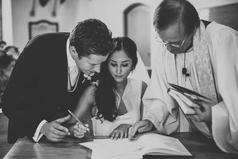 Bridebook.co.uk- bride and groom signing the register with the priest