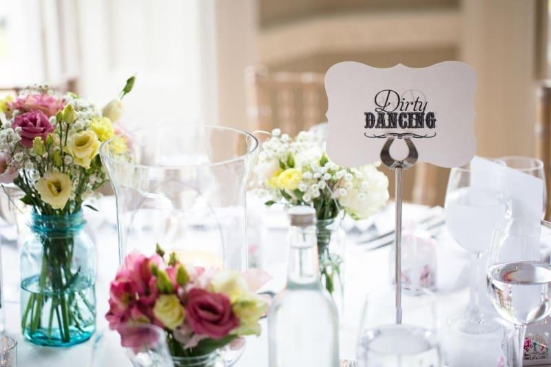 Bridebook.co.uk- dancing table name and flowers at wedding breakfast