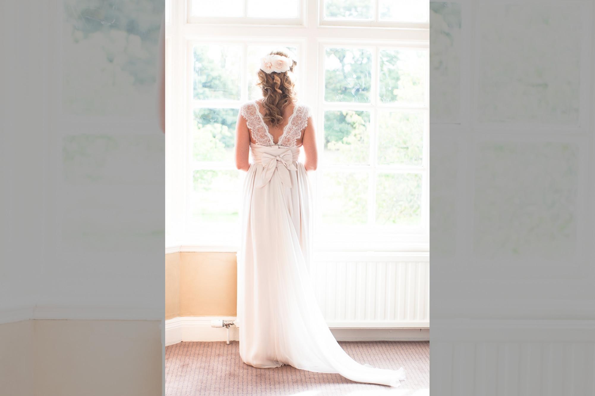 Bridebook.co.uk- bride in her gown facing the window