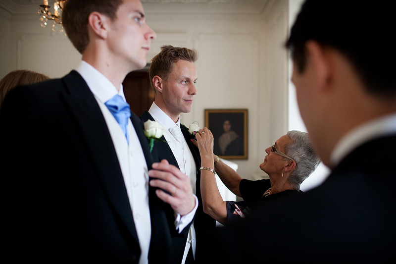 Bridebook.co.uk- groom and usher having their buttonnaires adjusted
