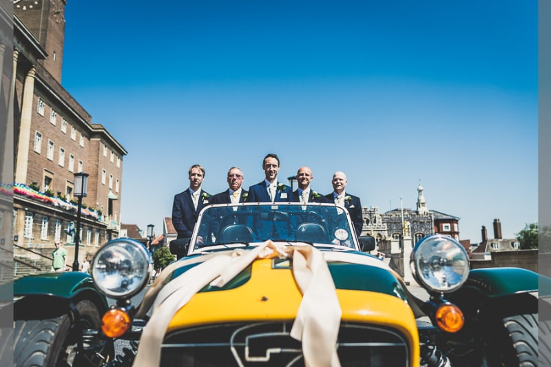 Bridebook.co.uk- groom and ushers standing in yellow sports car