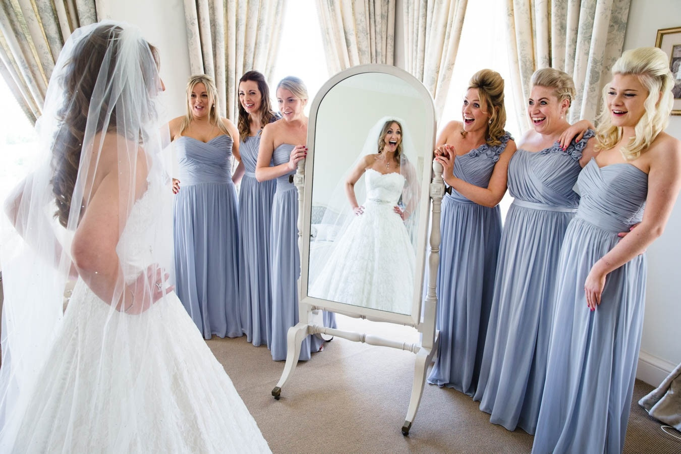 Bridebook.co.uk- bride reflected in mirror as bridesmaids see her for the first time